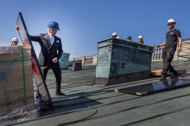 H.M. Konungen tar emot en uppackad solcellspanel.