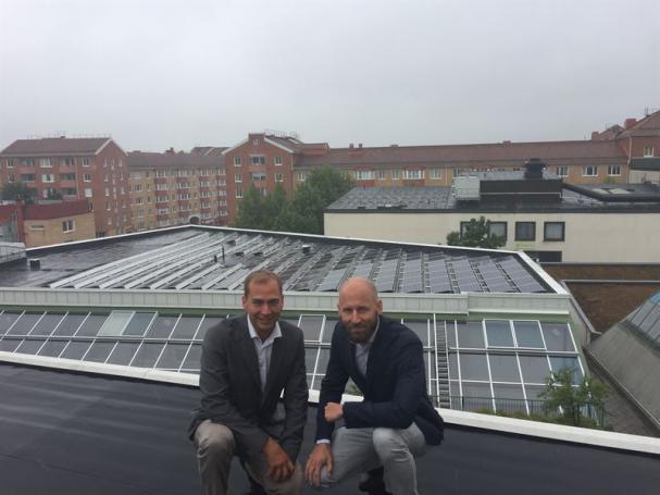Johan Lönneborg, Adven, och Magnus Åkesson, Citycon, framför solcellsparken i Jakobsbergs Centrum.