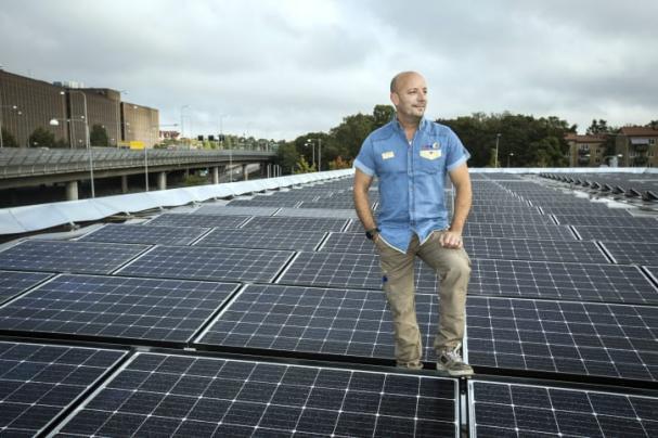 Säljchef Martin Garmstedt på OKQ8 Västberga står på stationens tak där solcellsanläggningen är installerad.
