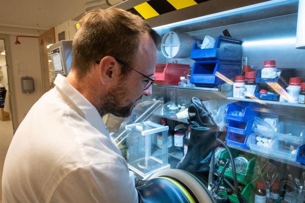 Nathan O'Brien vid handskboxen där de luft- och fuktkänsliga molekylerna syntetiseras.