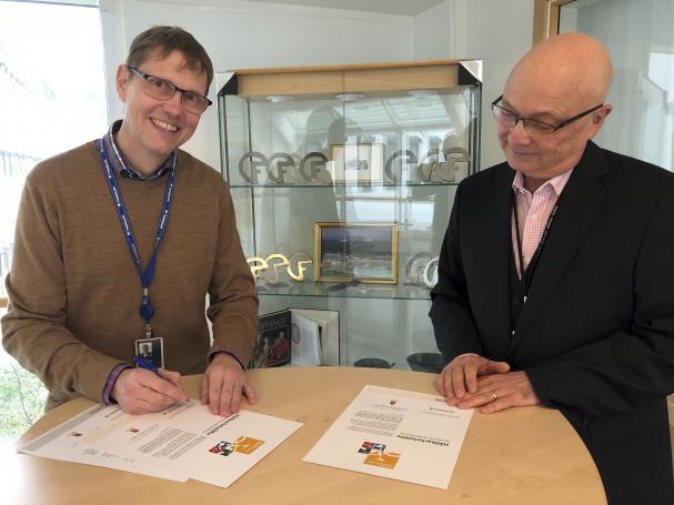 Vice vd Johan Börjesson (t v) signerar Forsmarks hållbarhetslöfte. T h Jonas Svensson, chef på skyddsavdelningen vid Forsmarks Kraftgrupp.